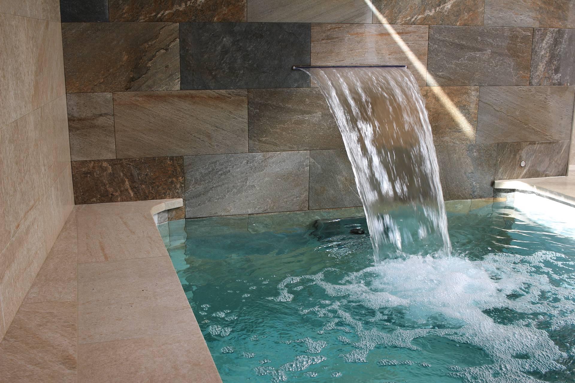 Piscina climatizada con cascada relax y decorativa.