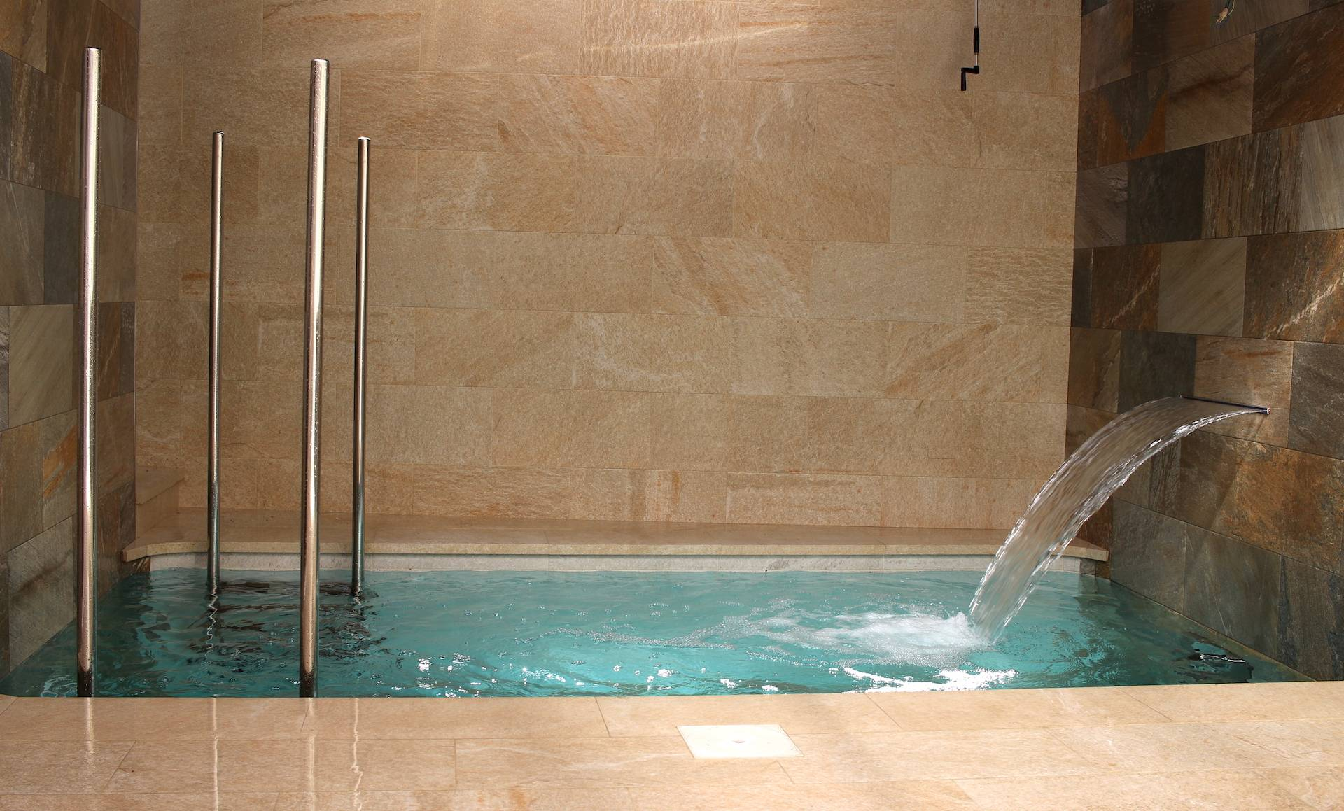 Construcción de pequeña piscina porcelánica salina, con cascada y equipo de natación contracorriente.