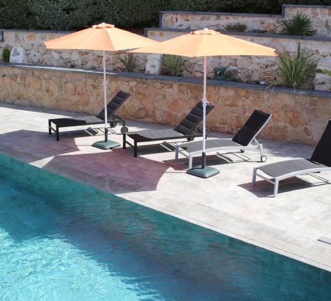 Zona de playa de piscina solada en gres porcelánico igual al revestimiento de la piscina.
