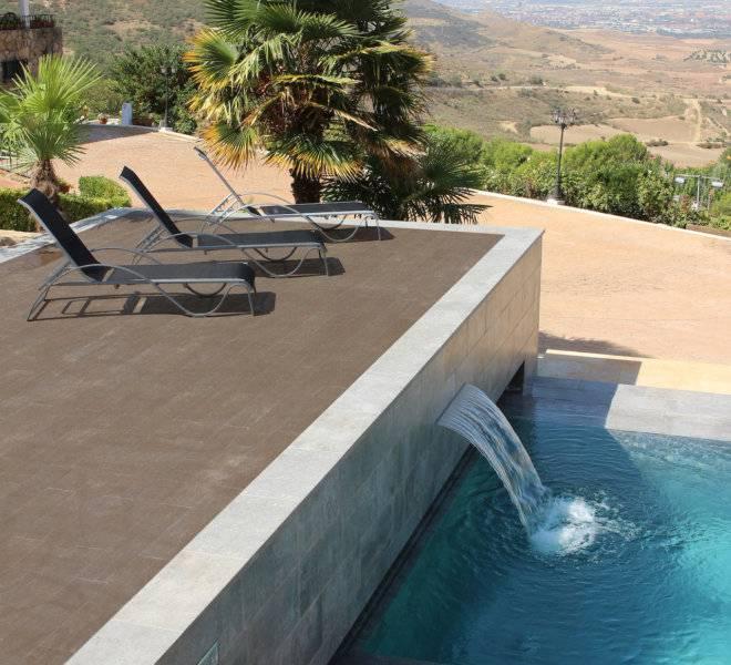 Construcción de piscina desbordante con cascada relax y decorativa