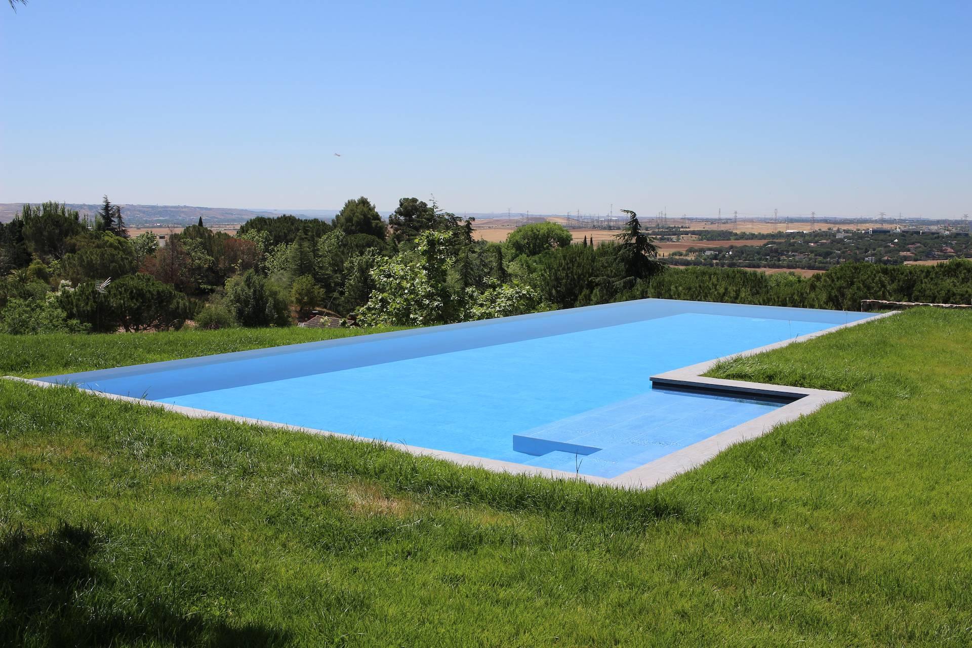 Construcción de piscina en L desbordante infinita en Madrid