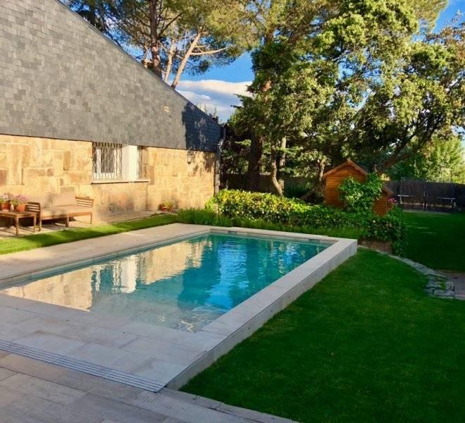 Jardín con piscina estilo rústico.