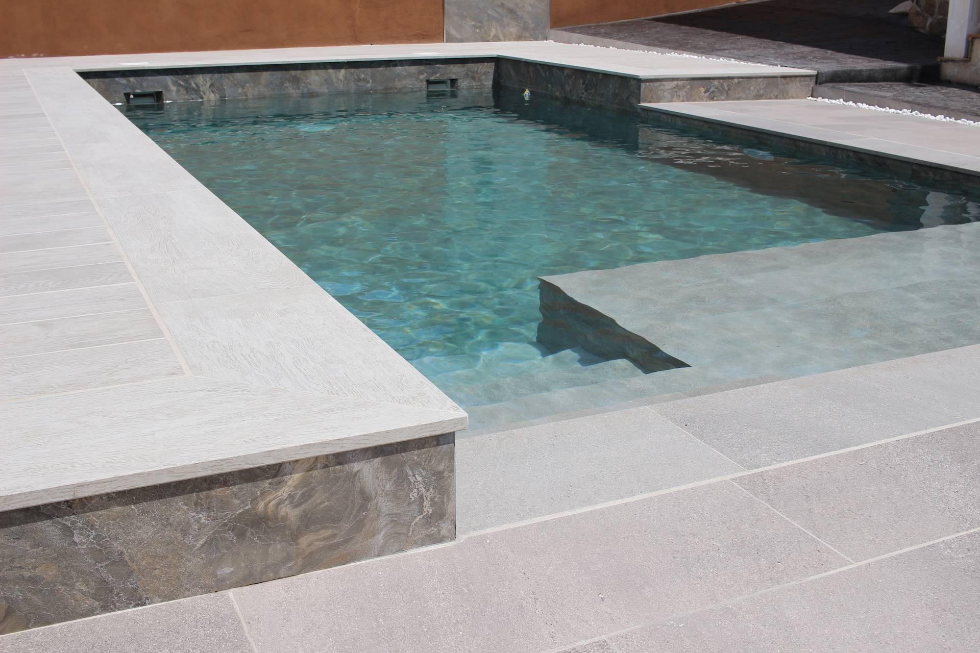 Exterior de piscina en dos alturas combinando el gres porcelánico