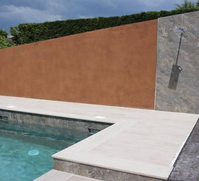 Ducha encastrada en pared con alicatado igual al revestimiento de piscina.