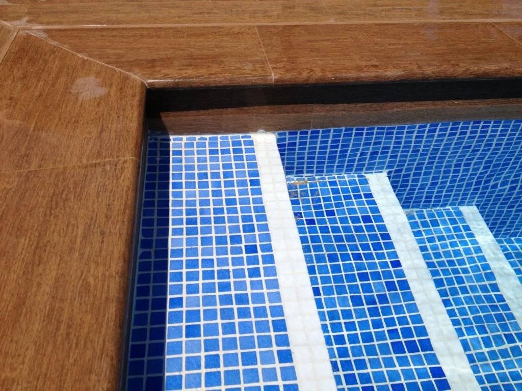 Interior de piscina en gresite y borde en porcelánico imitación madera