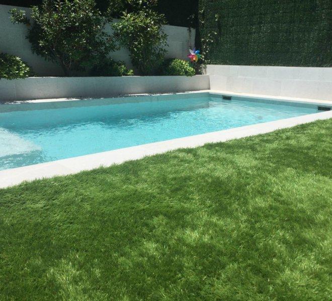 Diseño de piscina y jardín con zona verde y jardinera.