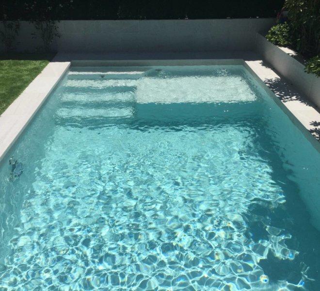 Diseño y construcción de piscina con escalera también de obra y cama de agua