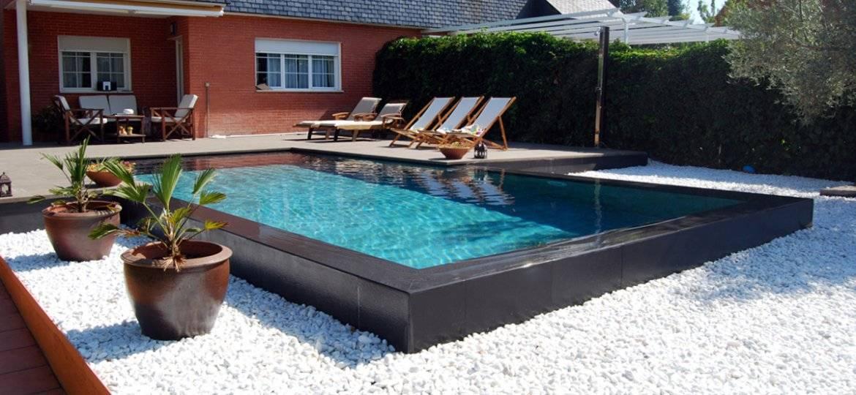 Piscina Desbordante Tipo Zen. El desborde en cascada sobre piedra blanca se hace por una zona marcada en negro.