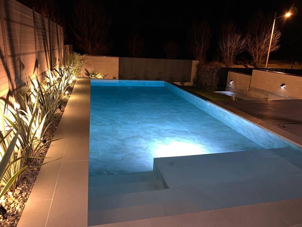 Piscina con desborde infinity e iluminación suba acuática.
