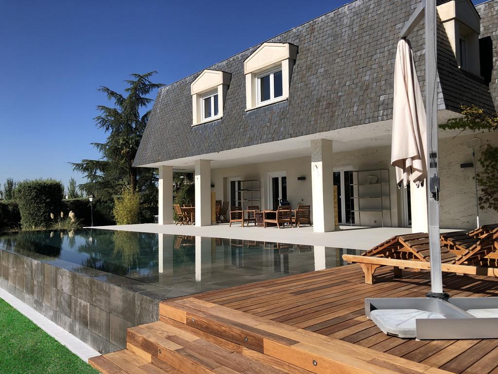 Construcción de piscina de lujo en vivienda colonial de estilo infinity
