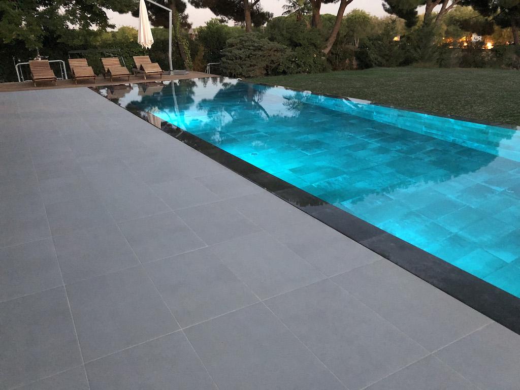 Construcción de piscina desbordante con iluminación subacuática en rgb.