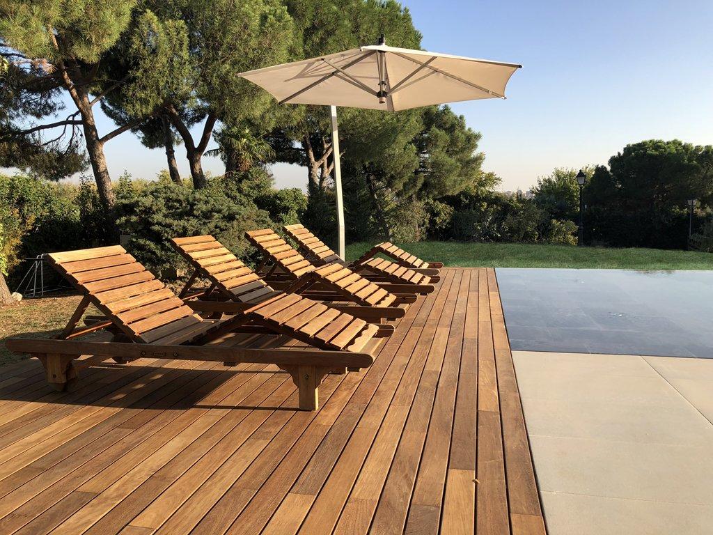 Construcción de piscina en Madrid de estilo infinita. Revestimiento porcelánico y exterior en porcelánico combinado con madera.