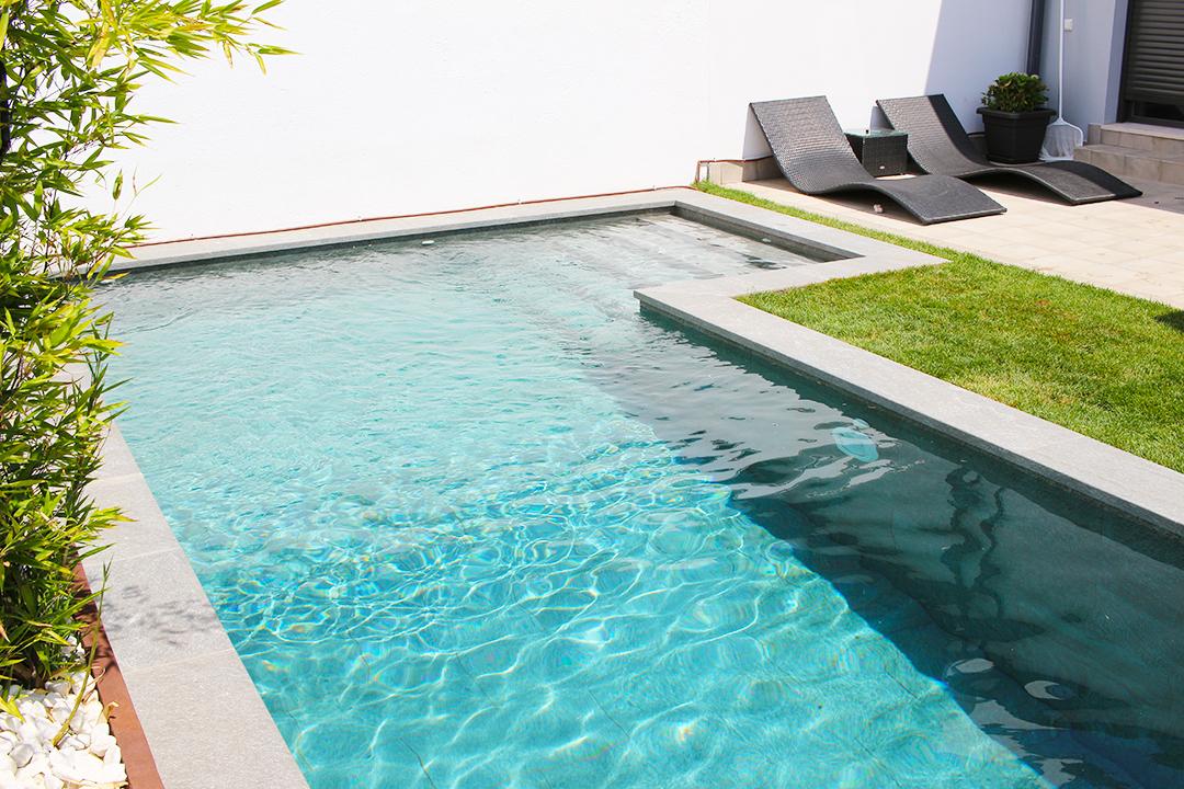 Construcción de piscina en forma de L con interior en negro.