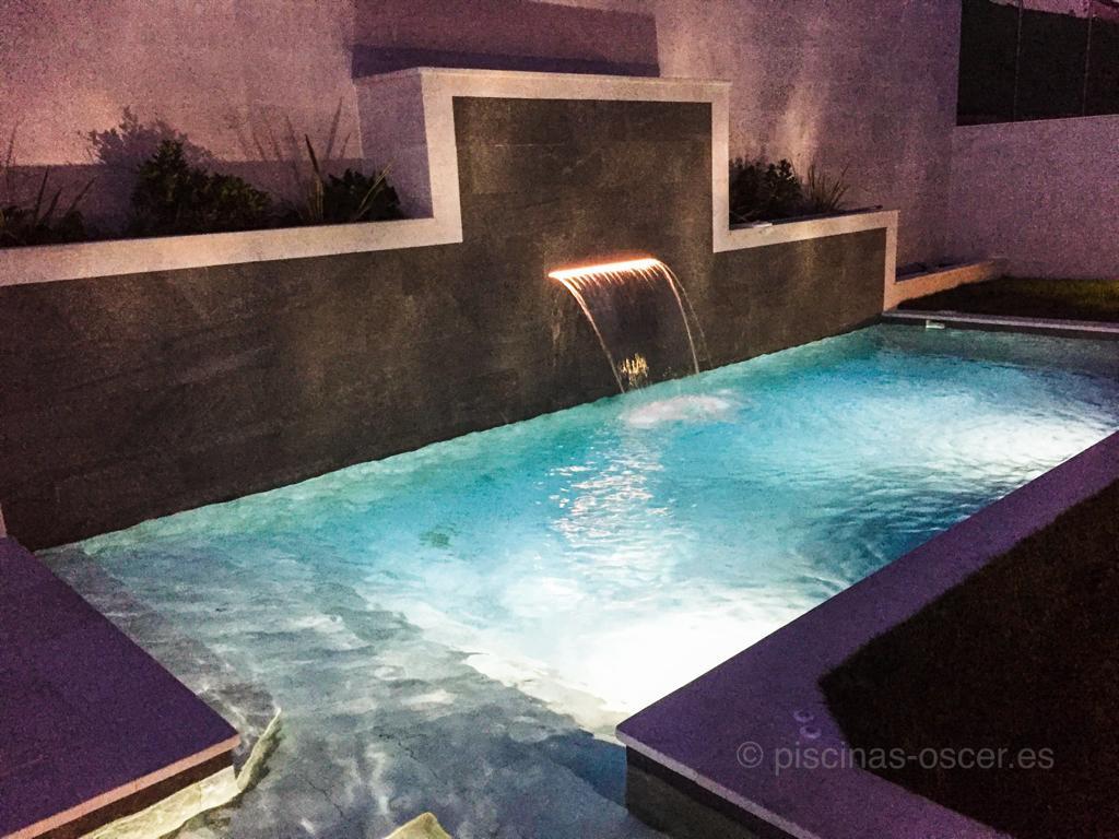 Cascada con iluminación led en muro de la piscina