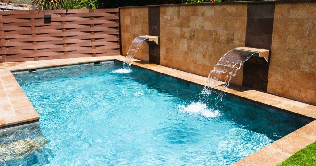 Dos cascadas saltan del muro para caer en la piscina