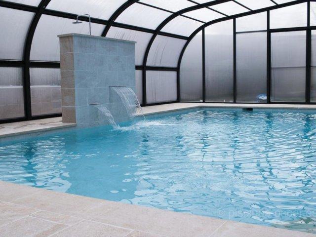 Piscina con cubierta elevada y cascadas decorativas y relax