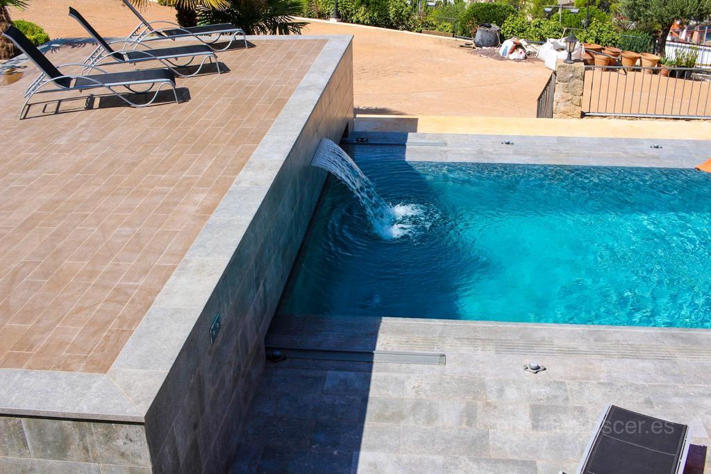 Solarium de piscina con cascada decorativa