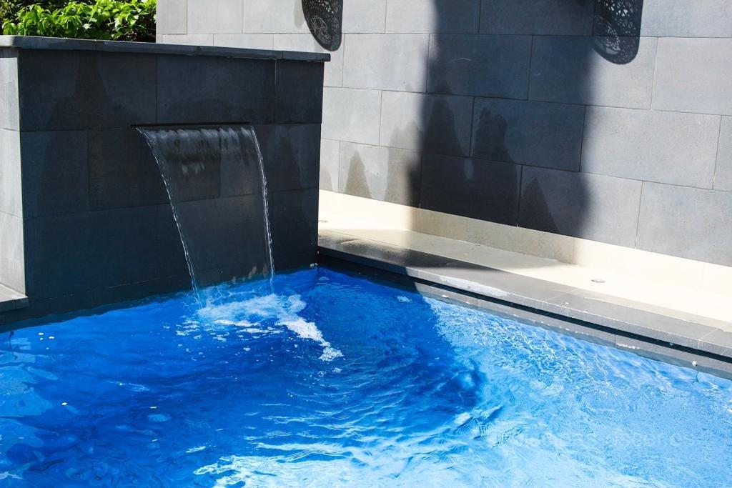 Piscina con porcelánico azul y cascada relax y decorativa
