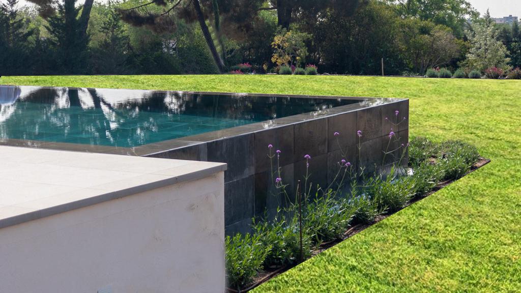 Piscina con desborde en cascada sobre rejilla oculta e integrada en el jardín