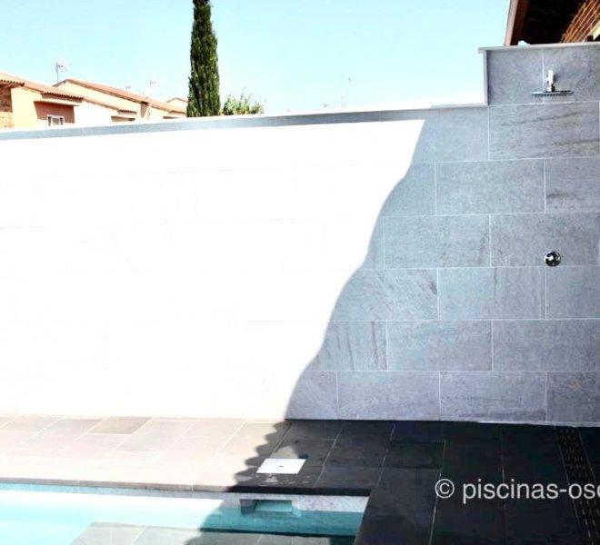 Ducha de piscina encastrada en el muro de una de las paredes de la parcela.
