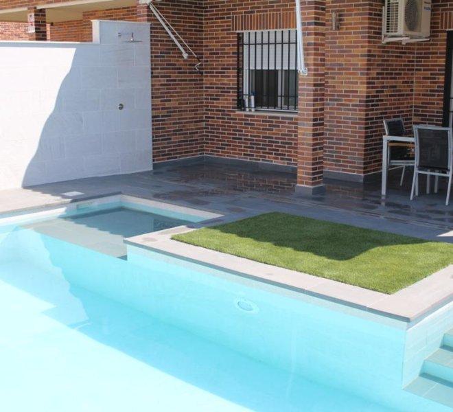 Diseño de piscina con escalera y cama de agua fuera de la zona de baño.