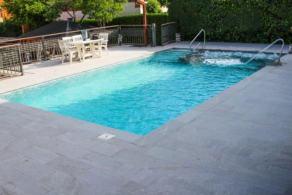 Spa o jacuzzi en interior de piscina porcelánica con playa exterior en porcelánico