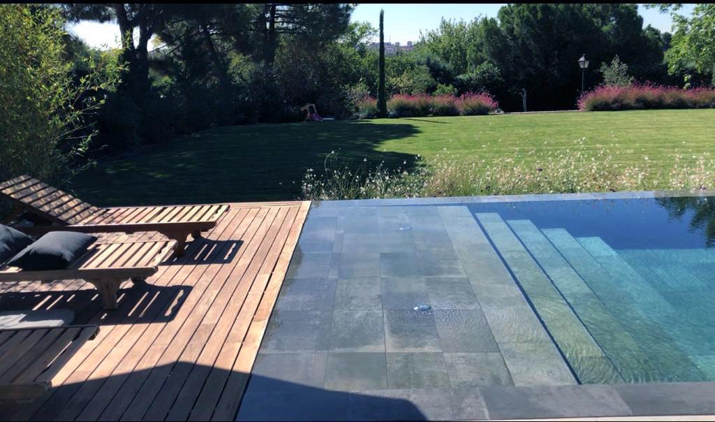 Zona de solarium húmedo y seco en piscina negra porcelánico