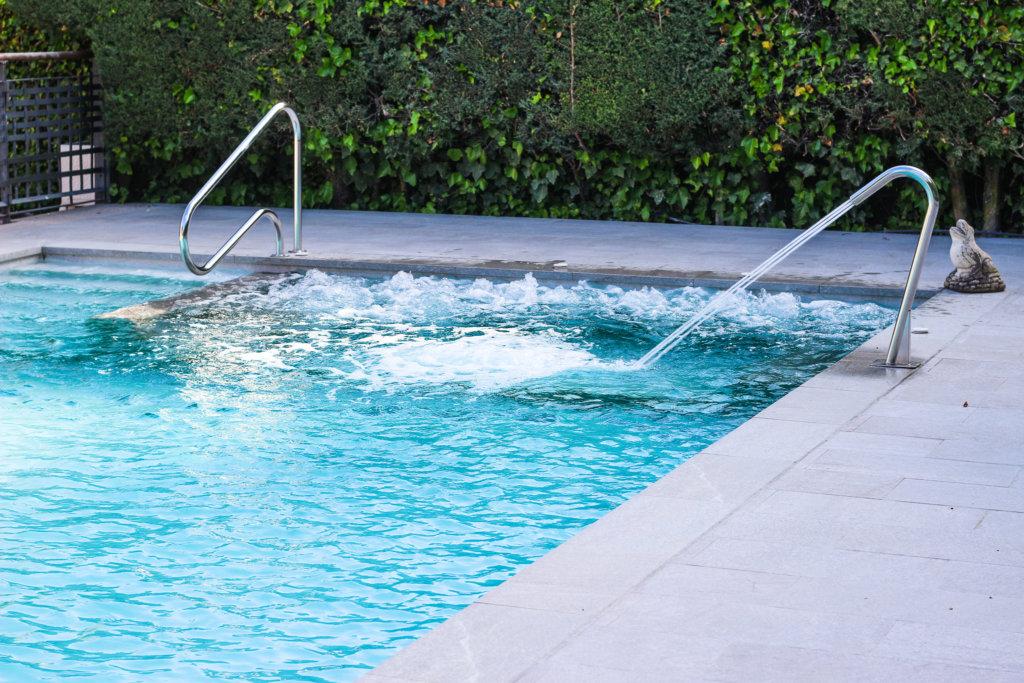 Pasamanos en piscina con jacuzzi interior y cascada cuello cisne