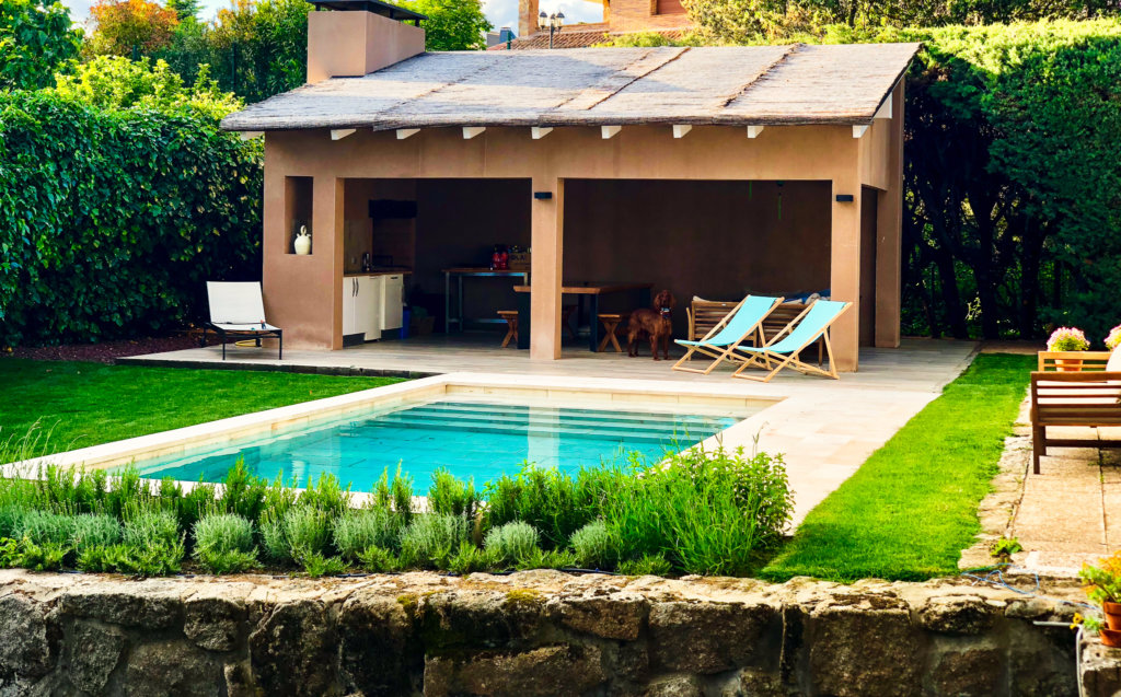 Jardín con porche junto a piscina, totalmente adaptada al espacio e integrada en el.