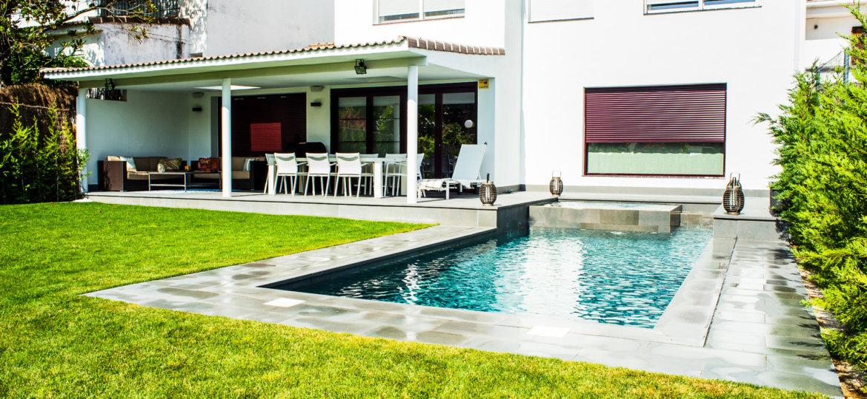 Diseño de piscina alargada con porcelánico interior en color gris