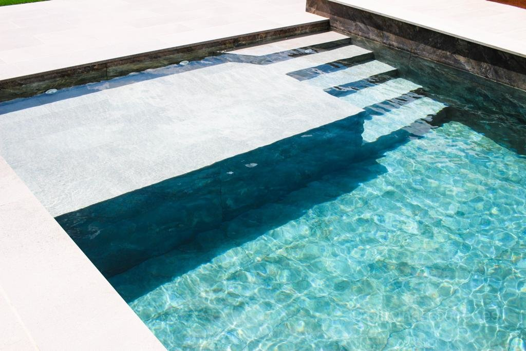 Diseño de escalera en interior de piscina con cama de agua
