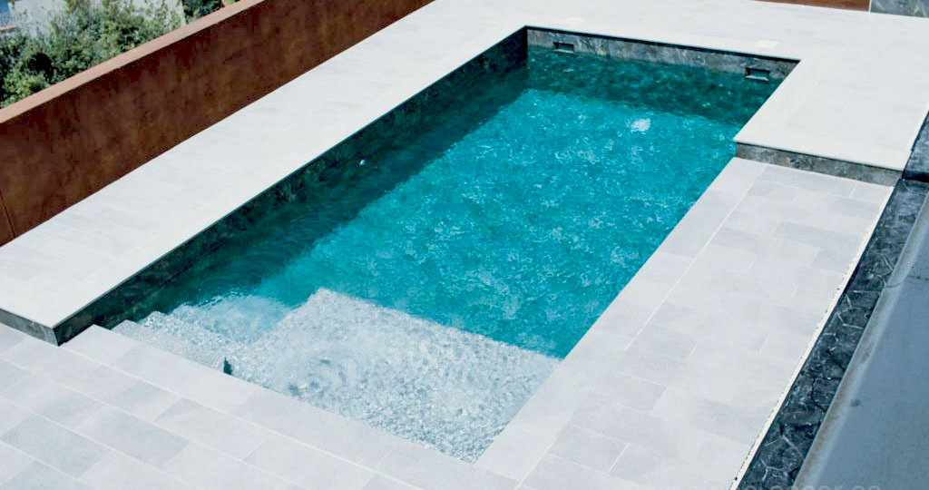 Inspiración de piscina de obra moderna, con diseño en dos alturas.
