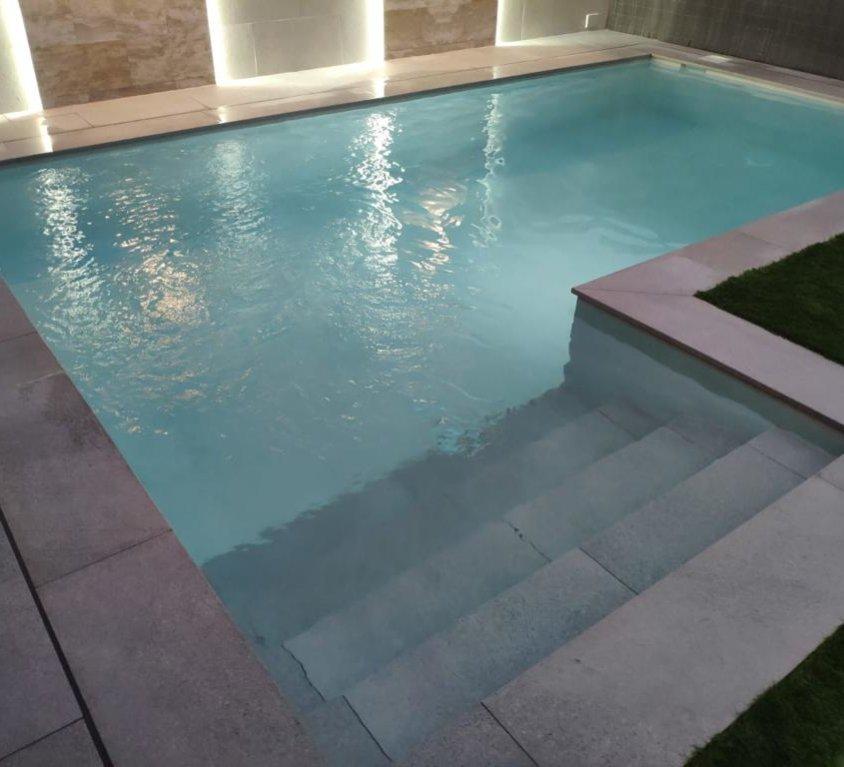 Modelo de piscina con escalera de obra en L